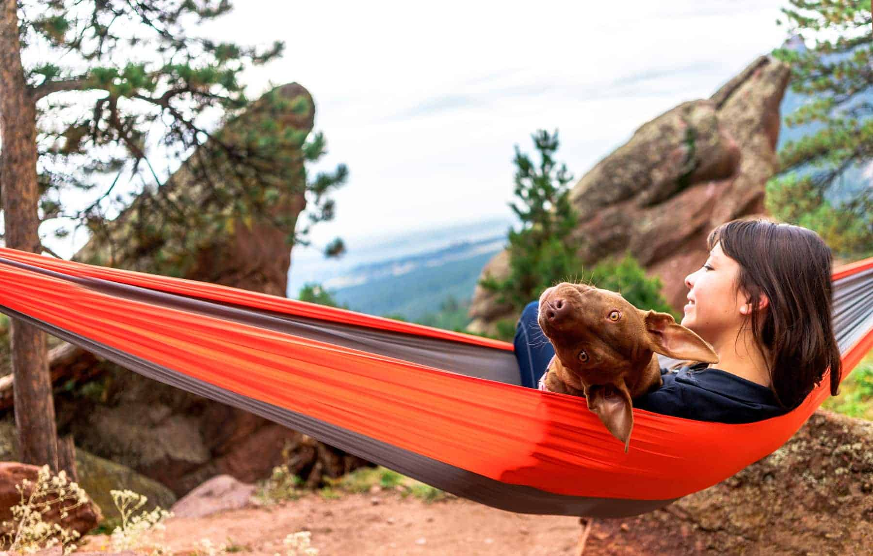 Young woman and dog in a custom hammock hanging in the mountains.